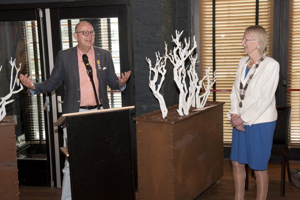 De heer Knijnenburg achter een spreekgestoelte met daarnaast burgemeester Ravestein