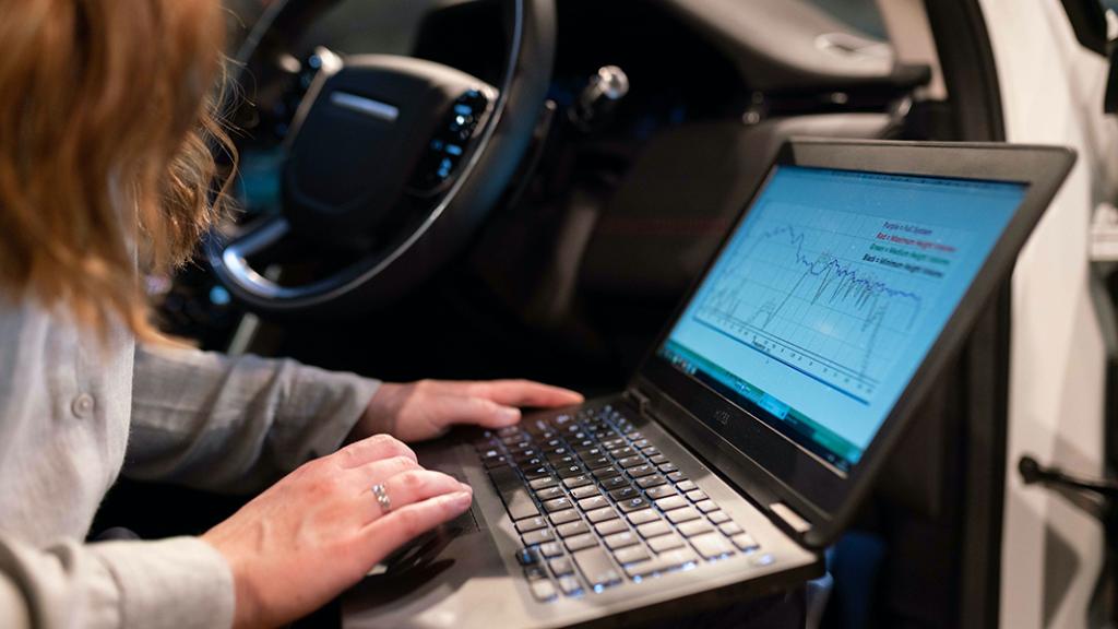 persoon op passagiersstoel auto met laptop met geluidsgrafiek op schoot