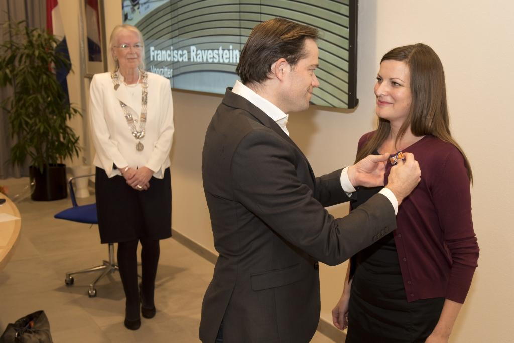 Wethouder Van Bijnen krijgt koninklijke onderscheiding opgespeld door haar partner
