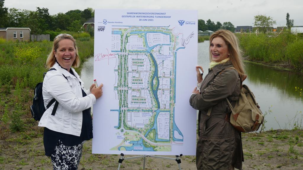 Wethouder Ilona Jense en hoogheemraad Manita Koop houden een bord vast met daarop het ontwerp van slimme waterberging Meander in Tuindershof Pijnacker